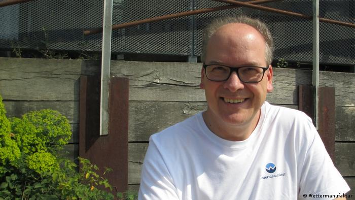 Jörg Riemann sitting against a wooden backdrop