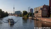 A boat on the river Spree running through the heart of Berlin. The tall TV tower is visible in the background