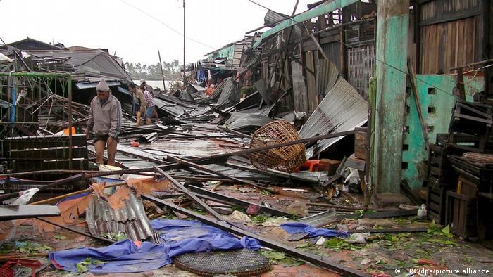 Rua coberta por entulhos de casas destruídas. Pessoas caminham entre os escombros.