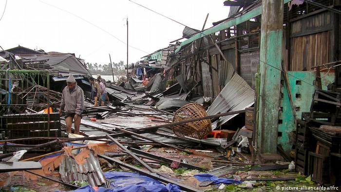 Myanmar villagers search for their belongings in the debris of houses caused by Cyclone Nargis