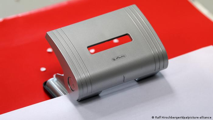A hole punch with red paper