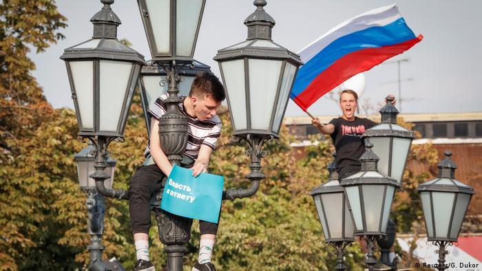 Молодые участники протестной акции в Москве 9 сентября 2018 года на фонарных столбах: один с плакатом Власть к ответу, другой - с флагом России.