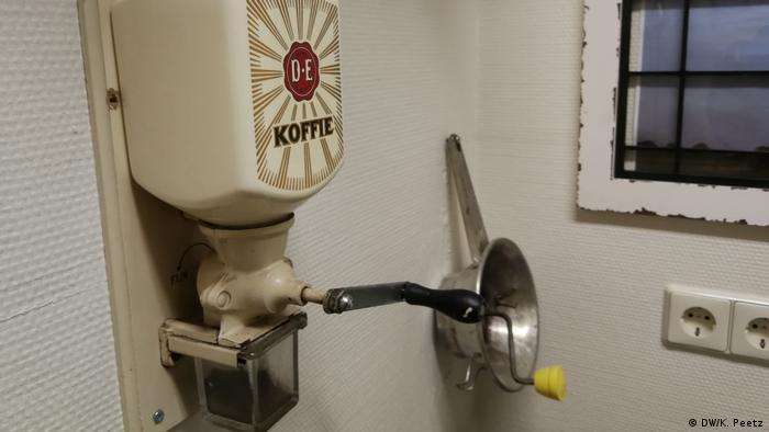 Eine alte Kaffeemühle hängt an einer Wand