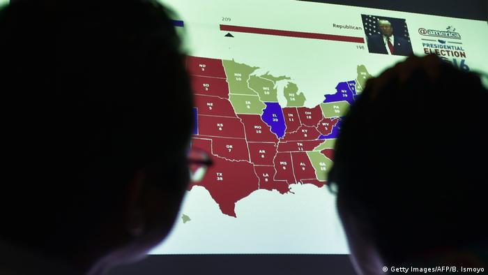 Dark faces watch a US election screen