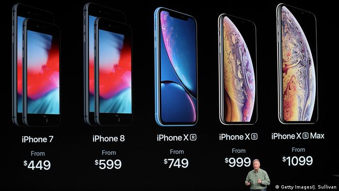 Phil Schiller, senior vice president of worldwide marketing at Apple, speaks during the Apple event. Several iPhone handsets and their prices can be seen in the background.