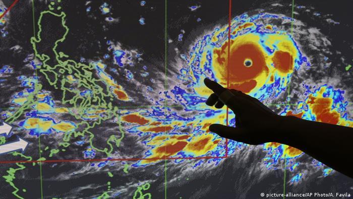 Filipino forecaster Meno Mendoza illustrates the path of Typhoon Mangkhut