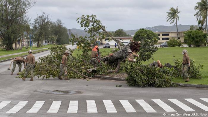 Sailors attached to Naval Mobile Construction Battalion (NMCB) 1, Detachent Guam, remove debris on Naval Base Guam