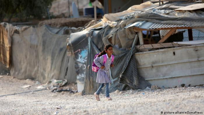 Ein Mädchen läuft vor einer Wellblechhütte entlang (Foto: picture-alliance)