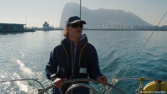 Filmstill aus Styx: Eine Frau steht am Steuer ihrer Yacht, hinter ihr das Meer und die Umrisse einer Stadt (Benedict Neuenfels)
