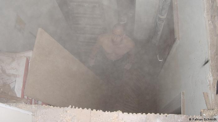 A man standing in a cloud of dust inside a building looking through a huge hole in the ceiling