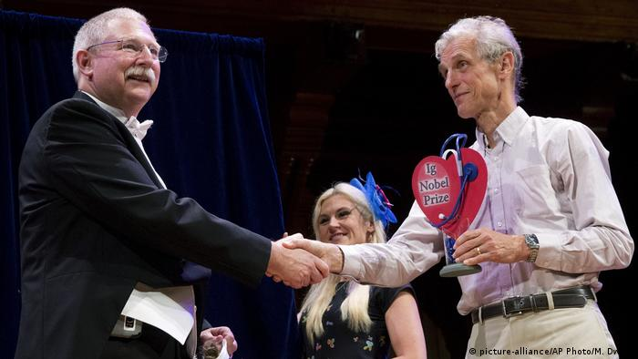 Wolfgang Ketterle shakes hands with David Wartigner who holds up his Ig prize heart award