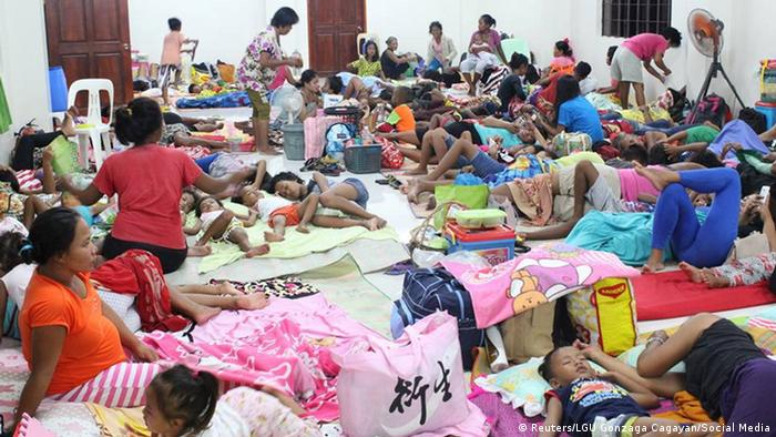 People are seen inside an evacuation centre