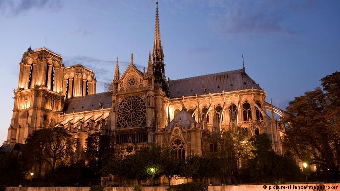 Vista vespertina da Catedral de Notre Dame do lado sul, com as torres ao fundo, do lado esquerdo, e destaque para a rosa de vidro em uma das alas laterais do edifício histórico
