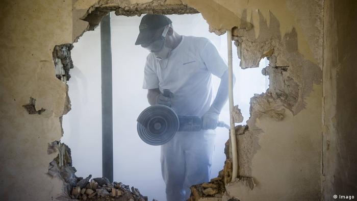 Handwerker bei der Kernsanierung eines Hauses mit viel Staub