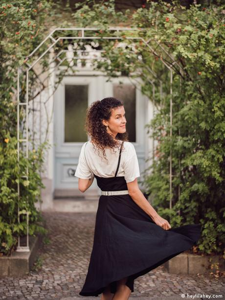 Fashion blogger Mia Marjanovic twirls in a black skirt and white t-shit under a garden arch