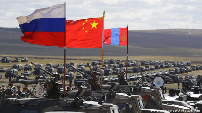 Russian, Chinese and Monoglian national flags wave above vehicles during the Vostok 2018 military exercises