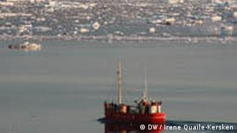 A ship out on the sea with ice bergs in the background
