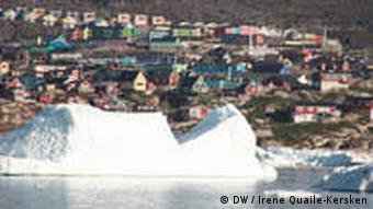 The town of Illulissat in the distance behind an ice berg