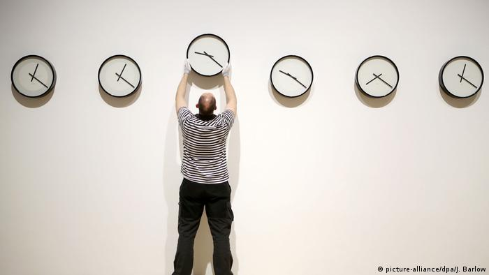 A man reaches up to hang a clock on the wall as different clocks next to it show different times (picture-alliance/dpa/J. Barlow)