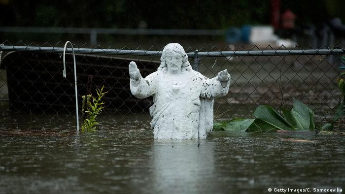 A statue of Jesus is seen partially submerged underwater
