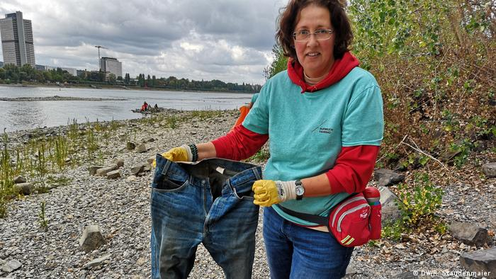 Volunteer Anke Mielke displays a pair of jeans she found while picking up trash along the Rhine River in Bonn, Germany (DW/R. Staudenmaier )