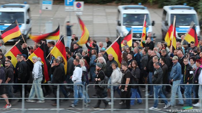 Demonstrators holding up German flags march through Chemnitz on Friday