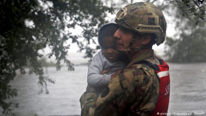 A serviceman carries a child