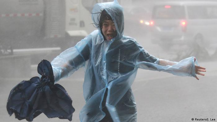 A woman runs in the rainstorm in Shenzhen (Reuters/J. Lee)