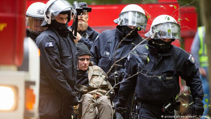 An activist gets carried away from Hambach forest by numerous policemen