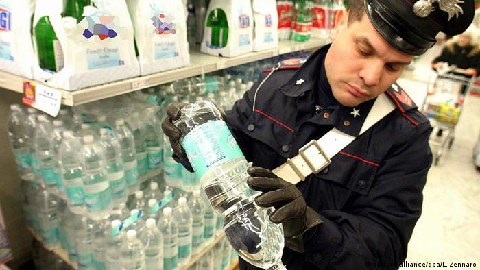 An Italian police officer inspects a bottle of mineral water in Genoa, Italy in December 2003 (picture-alliance/dpa/L. Zennaro)