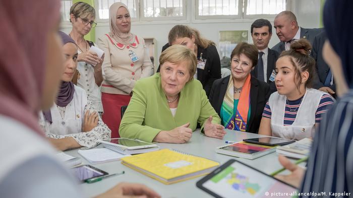 Merkel com meninas numa mesa de escola