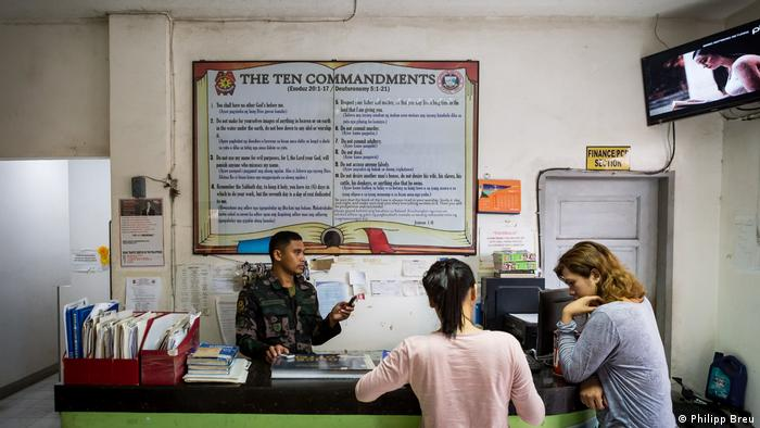 The biblical Ten Commandments hang on the wall above the reception desk at Ozamiz Police Station, Philippines (Philipp Breu)
