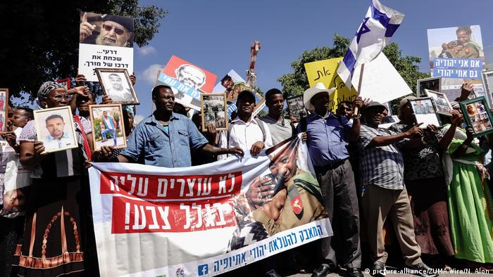 Ethiopian Jews hold banners and wave signs showing photos of family members still stranded in Ethiopia during a demonstration in Tel Aviv in 2015
