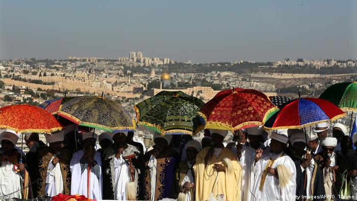 Religious leaders of the Ethiopian Jewish community hold colorful umbrellas as they celebrate the Sigd holiday, overlooking the city of Jerusalem in the background