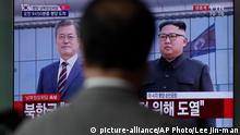 18.09.2018 A man watches a TV screen showing South Korean President Moon Jae-in, left, standing with North Korean leader Kim Jong Un upon his arrival at the airport in Pyongyang, North Korea, during a live news program at the Seoul Railway Station in Seoul, South Korea, Tuesday, Sept. 18, 2018. Moon landed in Pyongyang on Tuesday for his third summit this year with North Korean leader Kim. The letters read Pyongyang, Inter-Korean Summit. (AP Photo/Lee Jin-man)