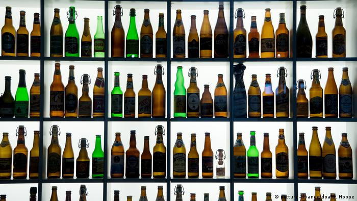Beers bottles stand illuminated in a cabinet (picture-alliance/dpa/S. Hoppe)