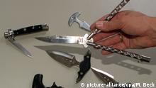 Springmesser (l), Faust- oder Fingermesser (unten, Mitte und oben) und sogenannte Butterfly-Messer (in der Hand), die am Dienstag (19.8.97) in der Hamburger Innenbehörde vorgestellt werden, sollen nach dem Willen der Hansestadt bundesweit verboten werden. Eine entsprechende Bundesrats-Initiative hat der Hamburger Senat angekündigt. Betroffen sind solche Messer, deren Verwendung bauartbedingt nur als Waffe denkbar ist. dpa (Zu lno) |