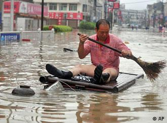 In this photo released by the Xinhua news agency, a man wades through the flooded street by home-made raft in Cangnan, east China's Zhejiang province, on Monday Aug. 10, 2009. A powerful typhoon toppled houses, flooded villages and forced nearly 1 million people to flee to safety on China's eastern coast before weakening into a tropical storm Monday. (Xinhua/Wang Dingchang) ** NO SALES **