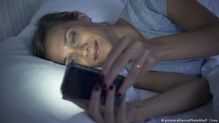 Frau benutzt Smartphone im Bett (picture-alliance/PhotoAlto/F. Cirou)