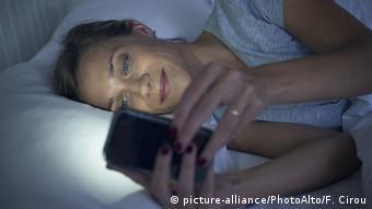 Frau benutzt Smartphone im Bett