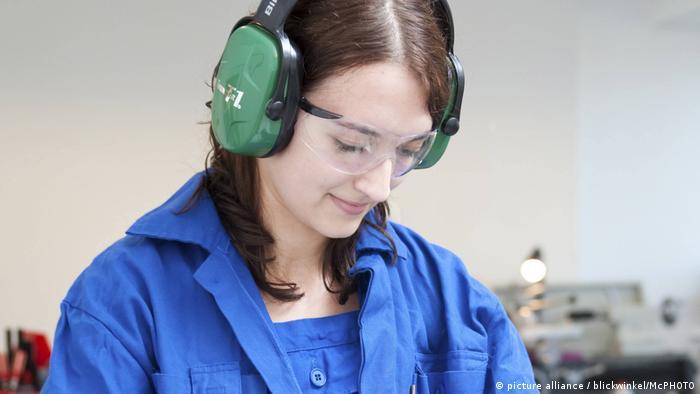 junge Frau arbeitet an Tischkreissaege, young woman works on a circular saw
