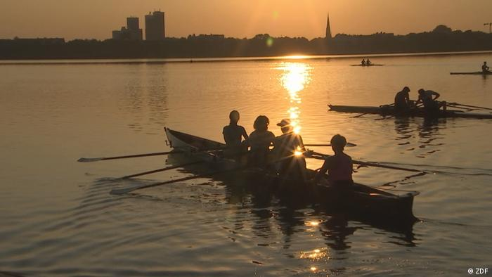 People out rowing on water as the sun sets