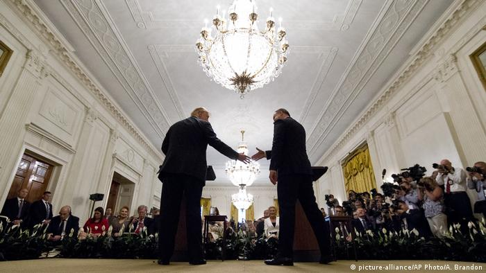 President Donald Trump, left, reaches to shake hands with Polish President Andrzej Duda