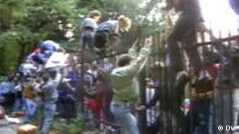 People climb the embassy fence