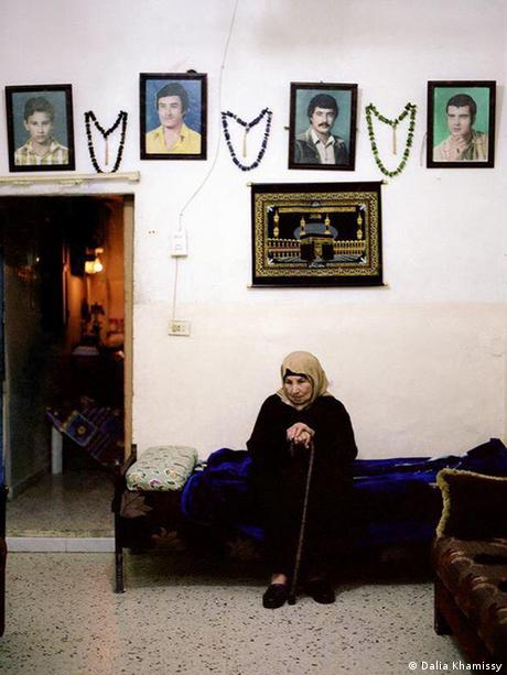 A woman sitting beneath the photos of her four sons