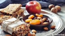 Ballaststoffe #8377653 Granola bars on plate with nuts and dried fruits on wooden background