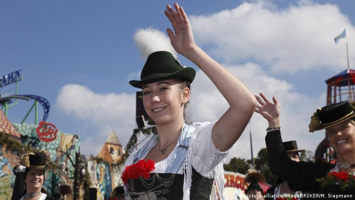 a women wearing a red ribbon waves (picture-alliance/imageBROKER/M. Siepmann)