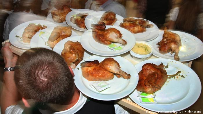 pieces of chicken on plates carried by a waiter (picture-alliance/dpa/K.-J. Hildenbrand)