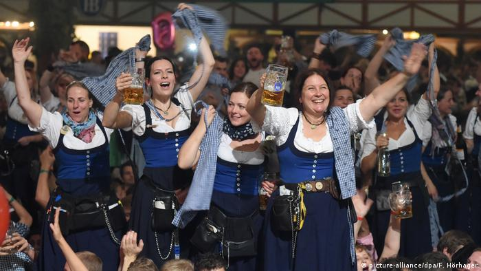 women dancing and holding beers in traditional garb (picture-alliance/dpa/F. Hörhager)