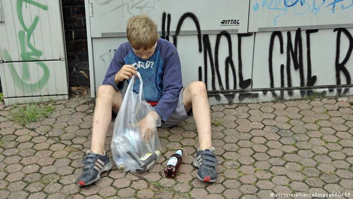 Junge verdient sein Taschengeld durch Sammeln von Pfandflaschen in Deutschland